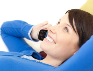 Attractive young woman talking on phone lying on a sofa